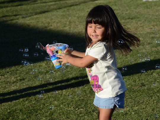 A girl plays with a bubble maker at  Fiesta Peoria