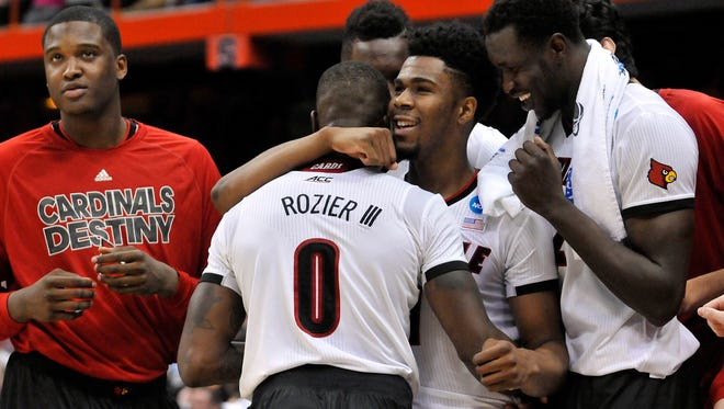 Louisville Cardinals guard Anton Gill (1) hugs guard Terry Rozier (0) during the second half against the North Carolina State Wolfpack in the semifinals of the East regional of the 2015 NCAA Tournament at Carrier Dome. Louisville won, 75-65.