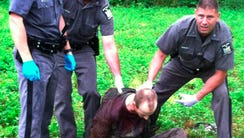 Police stand over David Sweat after he was shot and