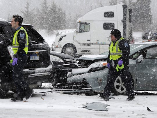 Emergency personnel help at the scene of a multi-vehicle pileup on I-94 in southern Michigan, on Friday, March 9, 2018.