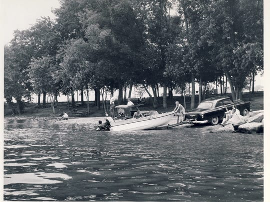 A boating party makes use of the launching area in Cox Park along River Road.  July 6, 1958.