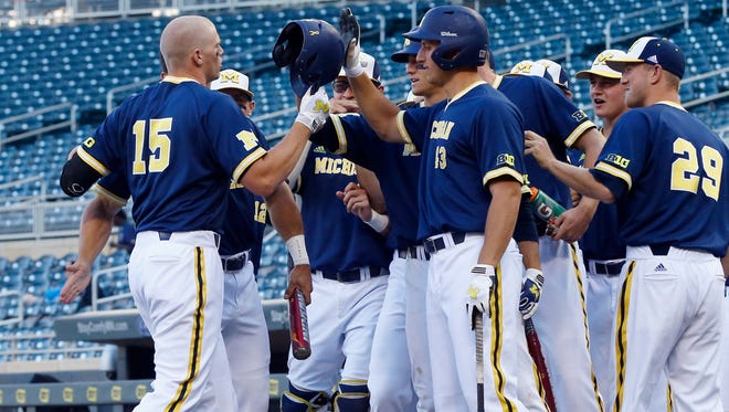 Michigan's Kendall Patrick, left, is greeted by teammates after his solo home run off Iowa pitcher Ryan Erickson in the fourth inning of the NCAA Big Ten tournament college baseball game, Thursday, May 21, 2015, in Minneapolis.