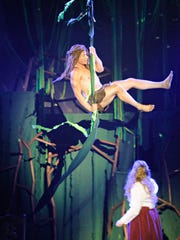 Tarzan, played by Kyle Seamans, swings on a vine over