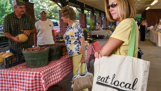 Robin Cathey of Anderson carries a cloth bag with produce she bought during her visit to the Anderson County Farmer's Market in Anderson on Saturday.