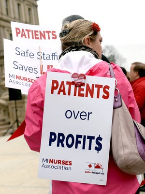 A protester wears and carries signs as she protests for passage of the Safe Patient Care Act Wednesday, March 23, 2016, in Lansing at the Capitol.