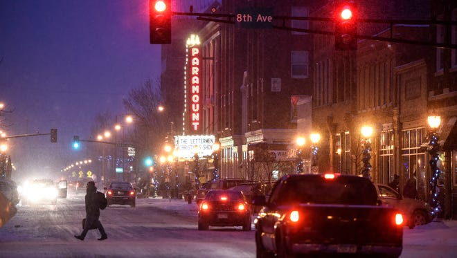 Light snow begins to fall in downtown St. Cloud Friday evening along St. Germain Street.