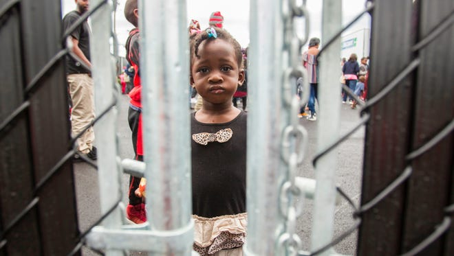 A girl who crossed the U.S.-Canada border illegally with her family in an effort to claim refugee status in Canada looks through a fence at a temporary detention center in Blackpool, Quebec, on August 5, 2017.
