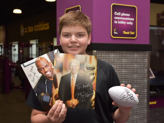 Noah Dietrich shows the signed photos and football