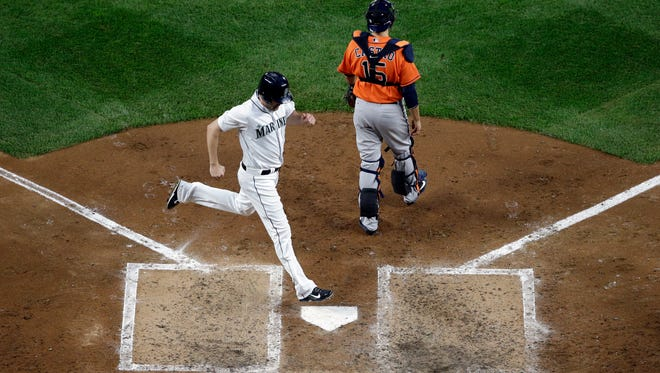 Seattle Mariners' Seth Smith, left, scores as Houston Astros catcher Jason Castro looks toward the field in the third inning of a baseball game Wednesday, April 27, 2016, in Seattle.