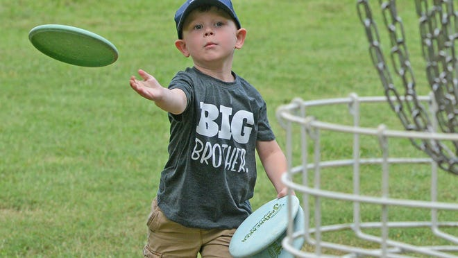Pierce Carroll, 4, works on his forehand putting technique at the disc golf course in Ben Geren Regional Park on Wednesday, July 22, 2020. Pierce was at the park with his father, Austin Carroll, who was trimming the grass around the tee boxes and baskets. The Western Arkansas Flying Disc Association will be holding it's 25th Hell on the Border disc golf tournament on Friday and Saturday on the three courses in the park.