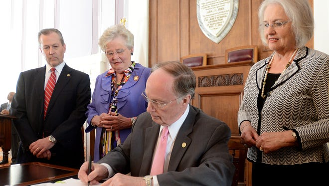 State Rep. Mary Sue McClurkin, right, a Republican from Indian Springs, Ala., stands behind Gov. Robert Bentley, center, as he signs House Bill 57, an abortion clinic regulation bill, on April 9, 2013. Speaker of the House Mike Hubbard and Lt. Gov. Kay Ivey also watched the signing.