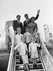 Sen. John F. Kennedy,  a Democratic presidential nominee in 1960, waves from a ramp as he and members of his traveling party get set to board a plane bound for Massachusetts. With him are his brother, Robert, left, and Robert's wife, John Kennedy's nephews and nieces:: Bobby Shriver, Bobby Kennedy Jr. and Kathleen Kennedy, and (front) Joe Kennedy, left, and David Kennedy.