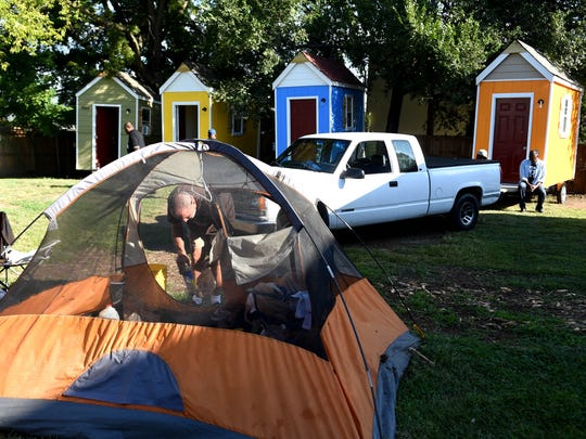 Roger McGue helps take down a friend's tent at a homeless encampment where six micro homes were delivered for the homeless on Friday Aug. 21, 2015