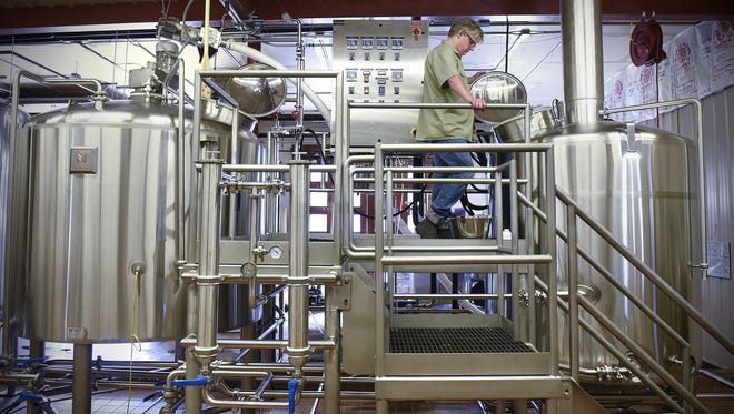 Beaver Island Brewing Co. brewmaster Chris Laumb checks on a batch of beer in the boil kettle at the brewery in St. Cloud. The craft beer industry has seen several local startups in recent years.