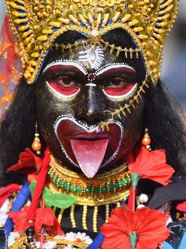 An Indian devotee dressed as the Hindu deity Kali attends