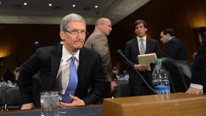 Apple CEO Tim Cook, shown here testifying in Congress in 2013, is battling the FBI over its request for a back door to a killer's iPhone.