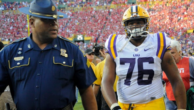 LSU guard Josh Boutte is escorted off the field after he was ejected from the game against Wisconsin late in the fourth quarter.