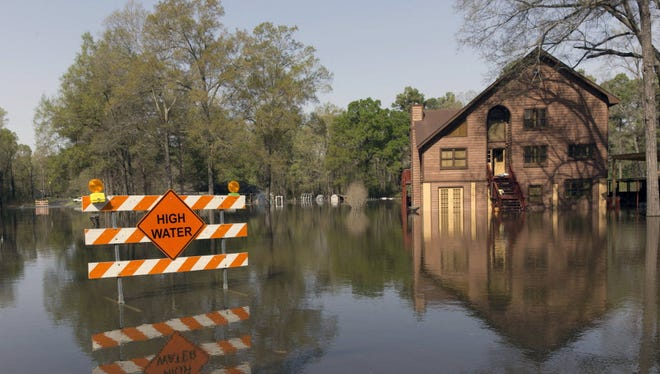 A sign marks high water in a flooded section of in Oil City, La., Sunday, March 13, 2016.