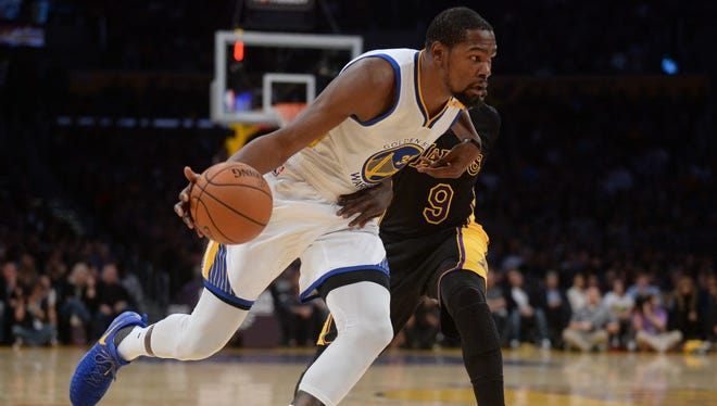 Warriors forward Kevin Durant (35) moves the ball against the Lakers during the first half.