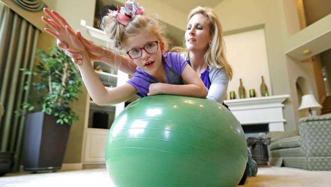 Stacey English, right, works on balance and core strength with her 7-year-old daughter, Addison, in Houston on Friday, June 23, 2017. Texas children with special needs like Addison have lost critical services since the state implemented $350 million in Medicaid cuts to speech, occupational, and physical therapy in December. (AP Photo/David J. Phillip)