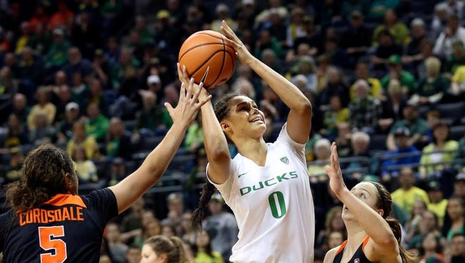 Oregon's Satou Sabally, center, shoots between Oregon State's Taya Corosdale, left, and Mikayla Pivec, right, during the first quarter of an NCAA college basketball game Sunday, Jan. 21, 2018, in Eugene, Ore. (Chris Pietsch/The Register-Guard via AP)