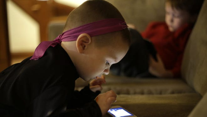 Two boys look at their smart devices in Boston, Massachusetts in 2014.