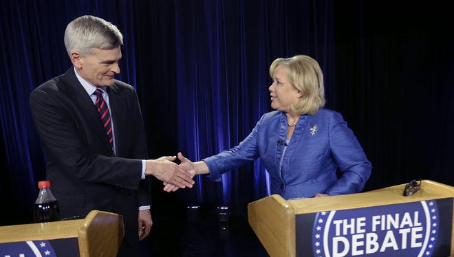 Sen. Mary Landrieu, D-La., and Rep. Bill Cassidy, R-La., greet each other before the start of their final debate for the Senate election runoff in Baton Rouge, La., Monday, Dec. 1, 2014. (AP Photo/Gerald Herbert)