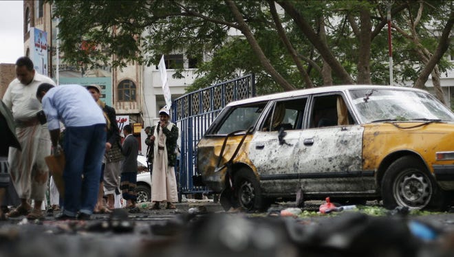 People gather at the site of a suicide bombing as Yemeni security officials collect debris in Sanaa, Yemen, on Oct. 9.