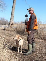 Reed Meyer of Franklin, Wis. and his dog pause on a