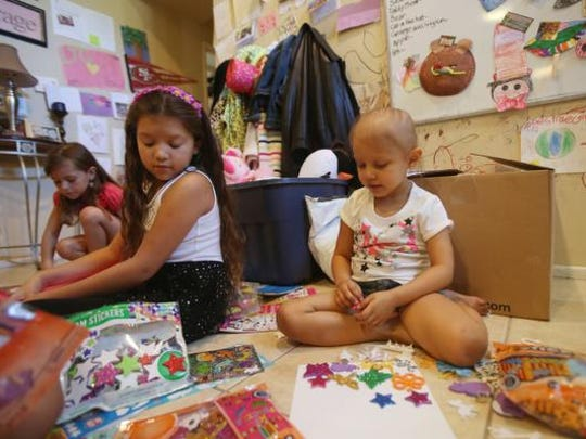 At far right, Desi Cechin, 5, who suffers from a brain tumor plays at home with her sister Dejah Saldovar.