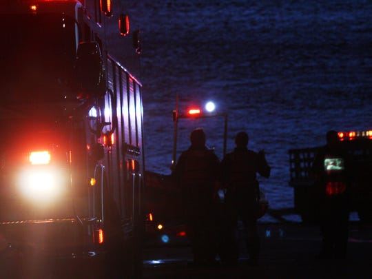 Fire officials talk among themselves after authorities discovered a dead woman's body in the Ohio River.