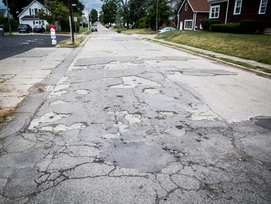 Cracks and potholes mar the pavement near the intersection