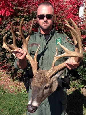 TWRA agent Eric Anderson holds the head and antlers of a large deer that was poached in Hendersonville on Monday.