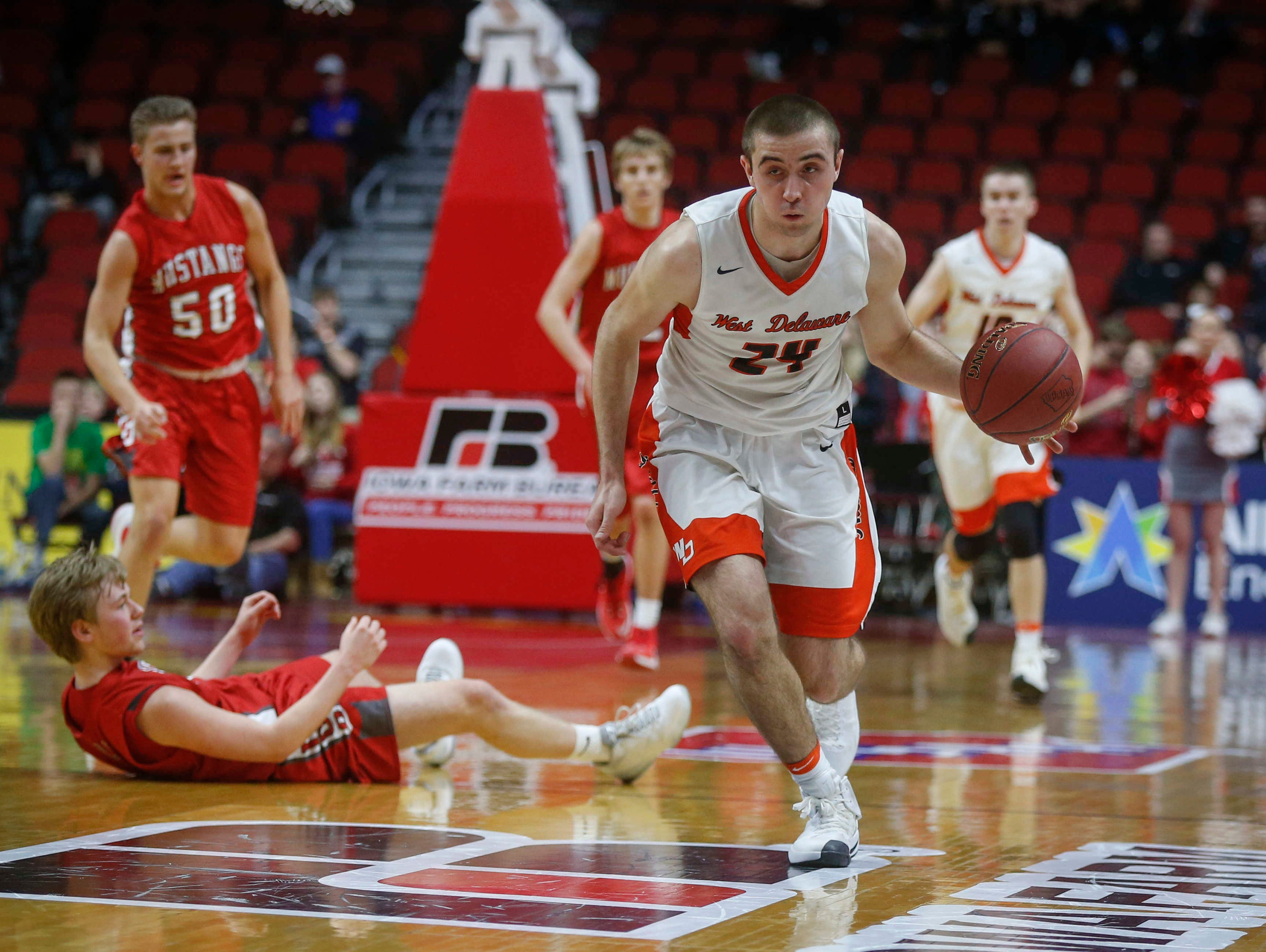 West Delaware sophomore Derek Krogmann scoops up a loose ball against Dallas Center-Grimes during the first round of the Iowa High School state basketball tournament at Wells Fargo Arena in Des Moines on Tuesday, March 7, 2017.