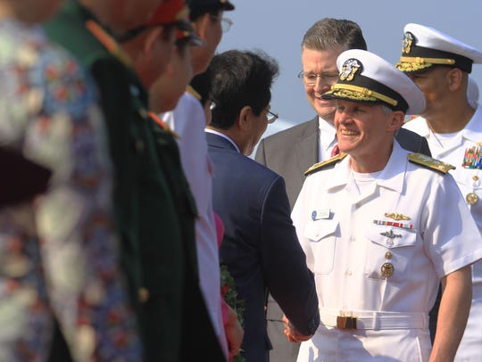 Vice Admiral Phillip G. Sawyer, right, commander of the U.S. Navy's 7th Fleet, greets Vietnamese officials after the aircraft carrier USS Carl Vinson pulled into port in Da Nang on March 5, 2018.
