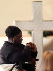 Geraldine McSwain of Butler bows her head as CEO of NewBridge Services, Robert Parker says Grace before more than 100 people enjoyed a feast at NewBridge Services 22nd annual Thanksgiving celebration at the First Reformed Church of Pompton Plains. November 25, 2015, Pompton Plains, NJ.