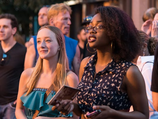 Nicole Lyn (right) and fellow musician Nicole Zell listen to Angela Sheik at the 2015 Ladybug Music Festival on Market Street in Wilmington.