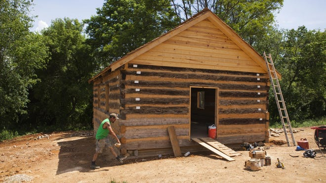 Stoney Caricofe, a carpenter with Frontier Culture Museum, carries stones as the Mount Tabor Log Church is restored May 27.