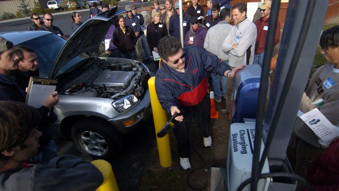 A file photo of the Electric Vehicle Program Manager for the City of Vacaville, giving a demonstration on how to recharge an electric car at a charging station in Truckee on Saturday, Oct. 8, 2005  as people attending the Truckee-Lake Tahoe High Performance Home-Green building Tour look on.