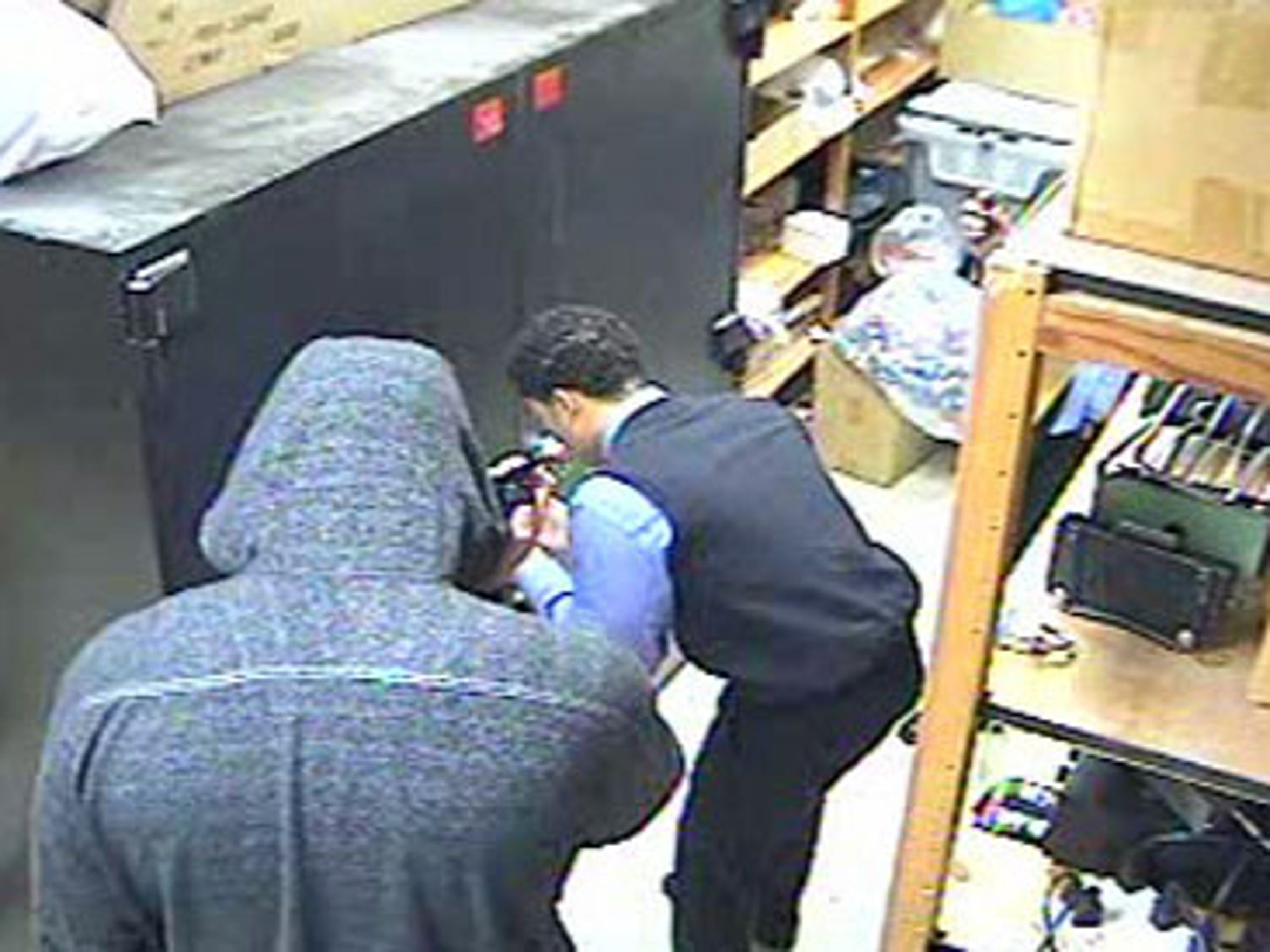 A surveillance-camera image introduced as evidence at trial shows Joel Thomas opening a cabinet in the vault of the Chase bank as Billy Wayne Brymer III holds a gun on him.