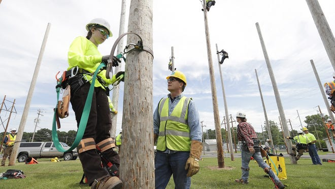 Great Lakes Energy Education Center student Jozie Hecker learns the particulars of climbing a utility pole with instructor Dan Scheider at Northeast Wisconsin Technical College Thursday in Green Bay.