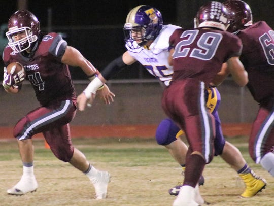 Tularosa's Toby Carrillo, left, finds a hole to run