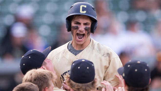 Evan Uhland of Cathedral High School, is pumped as he jumps into teammates' arms following his game-winning home run in extra innings against Penn High School, IHSAA 4A baseball state title game, Victory Field, Indianapolis, Saturday, June 17, 2017.