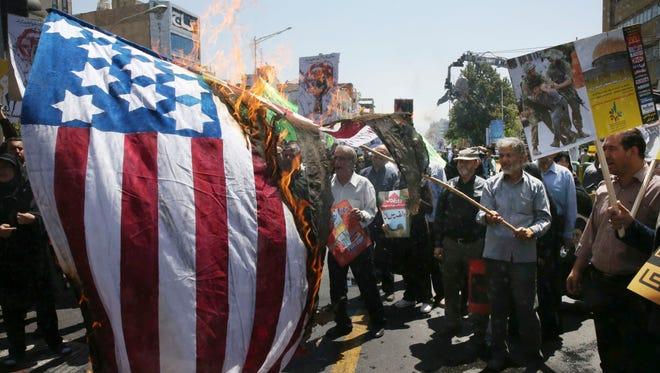 Iranian demonstrators burn a representation of the U.S. flag in Tehran, Iran, on July 10, 2015.