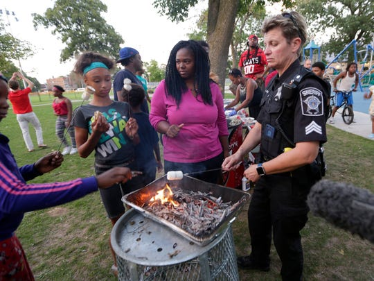 A Milwaukee County sheriff's deputy (right) cooks s'mores with people at Sherman Park, including County Supervisor Sequanna Taylor (second right), after it was determined the park would be open until 10 p.m.