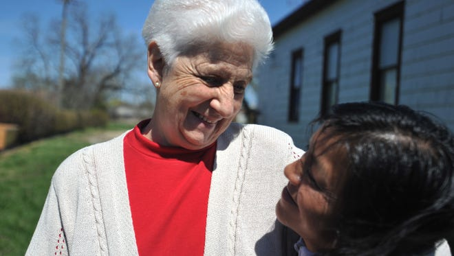Sister Rosa Alvarez holds Ilda Perez, who is losing her hair due to a cancer treatment, outside of La Esperanza in Georgetown.