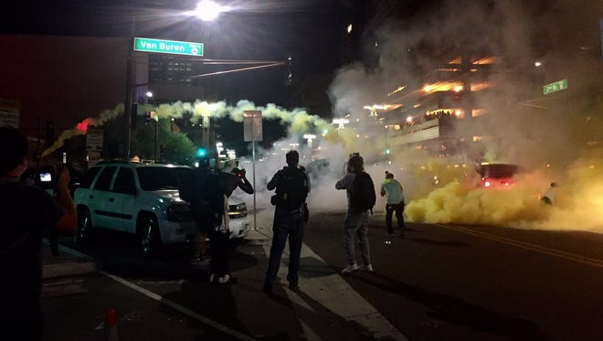 Police toss gas canisters at protesters in downtown Phoenix on Aug. 22, 2017, after President Trump spoke at the convention center.