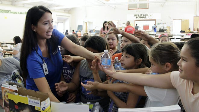 Brenda Zambrano, TRMC promotora de salud, hands out free bottles of water to summer school students at Heritage Elementary School in Tulare. The students learned about healthy eating and the sugars hiding in some of their favorite foods.