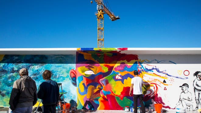 Local artist Juan Diaz, right, paints his section of a mural on an 148-foot construction wall on 5th Street & 5th Avenue South in downtown Naples on Sunday, Jan. 8, 2016. Seven local artists contributed to the temporary mural, which will stay up for the 18 month construction period of the future residental building.