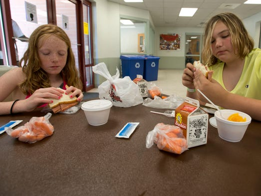 Ava Brown, 8, and Lea Hunt, 11, enjoys their Appetite4Life provided lunches while attending a city run summer camp.